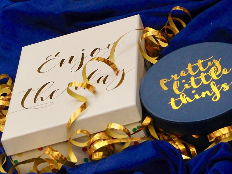 Geschenkboxen in weiß und blau mit gold