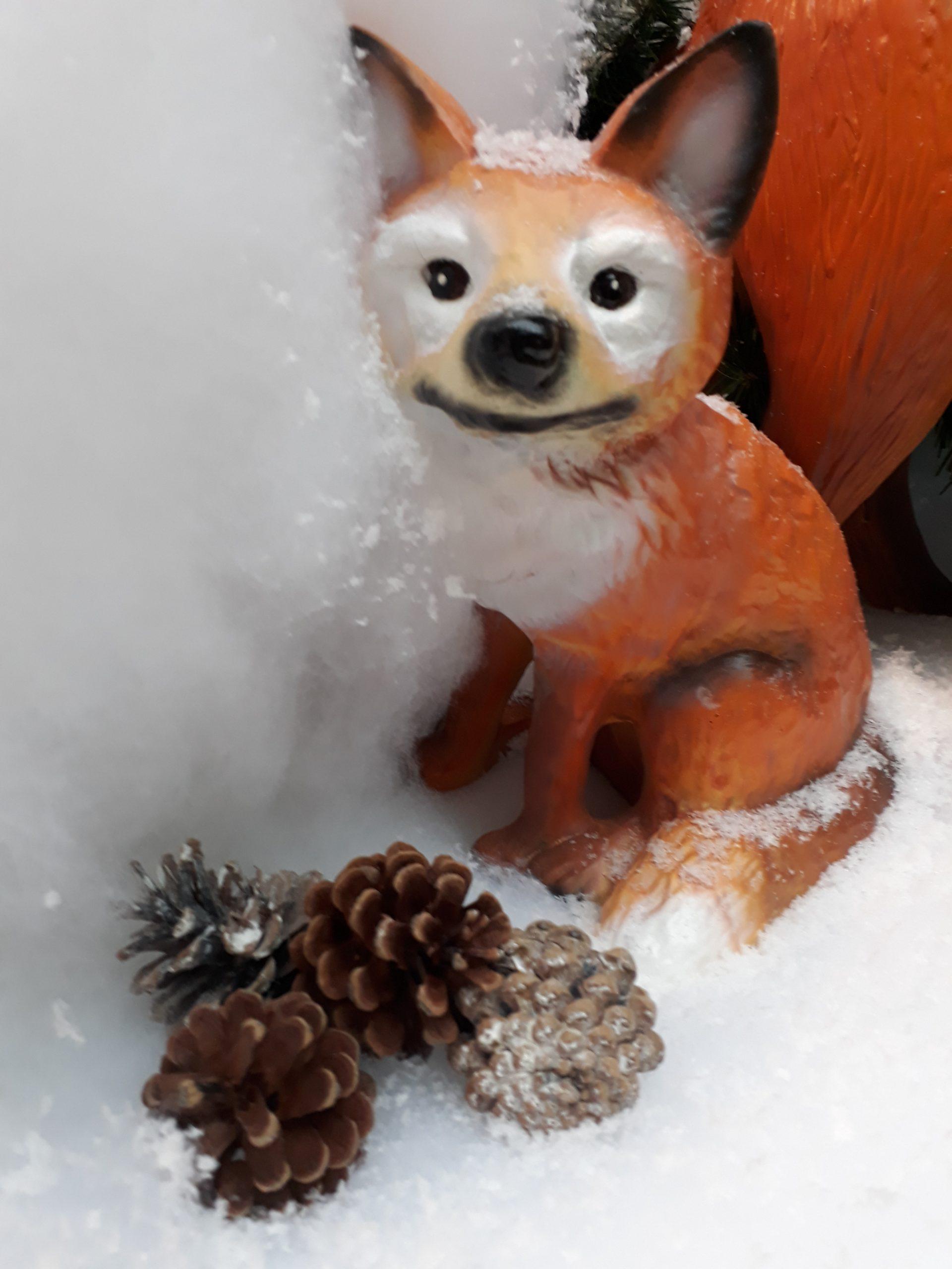kleiner Fuchs und Tannenzapfen im Schnee