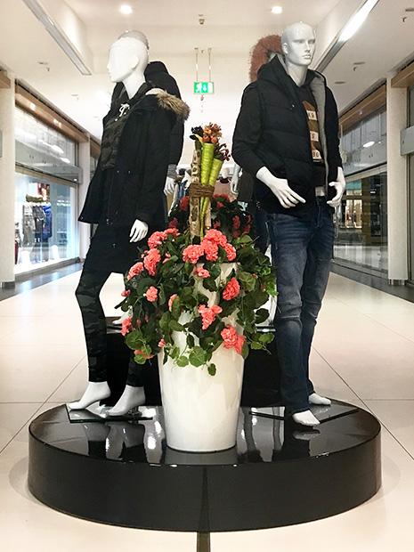 Statische Modenschau mit schwarzem Podest und Blumenvase