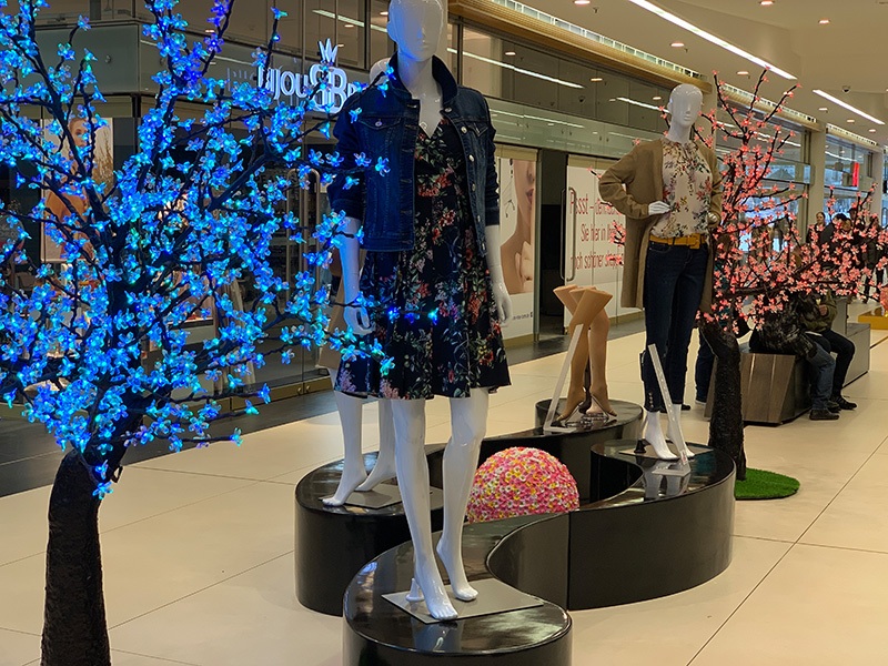 Statische Modenschau mit schwarzen Podesten und LED Baum
