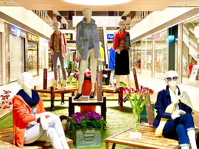 Schaufensterpuppen sitzen und stehen in Center-Dekoration