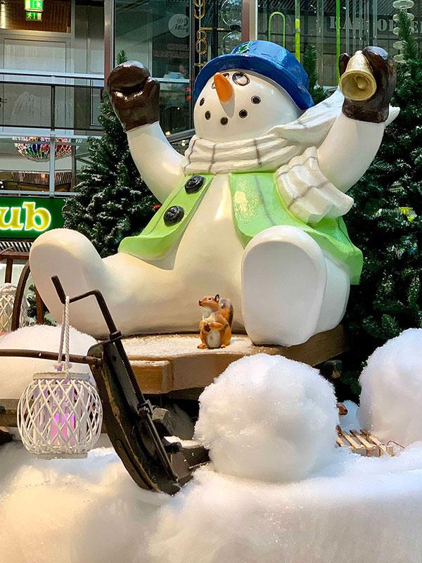 Riesiger Schneemann auf Schlitten der rodelt