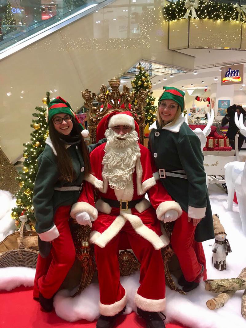 Weihnachtsmann sitzt auf Thron und Elfen stehen daneben