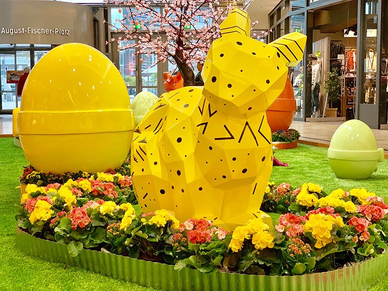 gelber Origamihase und Osterei mit Blumen