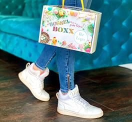 Junge Frau hält Bossel BOXX und läuft damit weg
